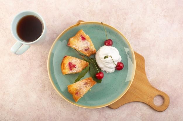 Een bovenaanzicht kersencake op het houten bureau met kersenroom en thee op het roze bureau cake koekje suiker zoet