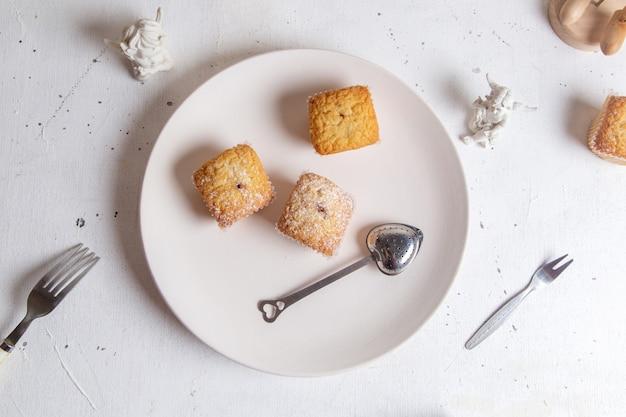 Een bovenaanzicht kleine cakes gebakken en lekker in papier vormen op het witte oppervlak