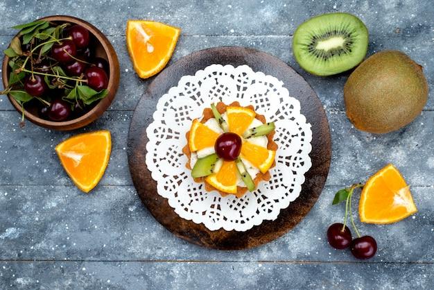 Een bovenaanzicht kleine heerlijke cake met room en vers gesneden fruit op het grijze bureau cake suikerthee