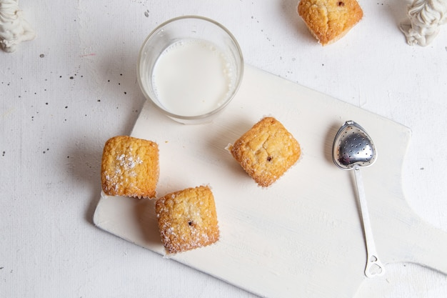 Een bovenaanzicht kleine lekkere taarten met suiker poeder en glas melk op het witte oppervlak