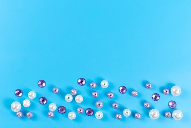 Een bovenaanzicht kleine ronde knoppen gekleurde sieraden details geïsoleerd op blauw, diamant kleur juwelen