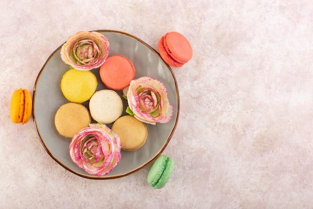 Een bovenaanzicht kleurde franse macarons met bloemen in plaat op het roze bureau cake koekje suiker zoet