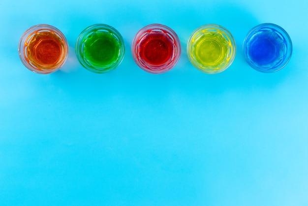 Een bovenaanzicht kleurrijke drankjes in transparante glazen op blauw, drink sap fruit kleur