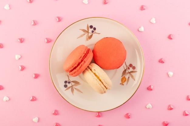 Een bovenaanzicht kleurrijke franse macarons binnen plaat op het roze van de het koekjessuiker van de bureaucake