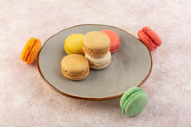 Een bovenaanzicht kleurrijke franse macarons lekker en heerlijk binnen plaat op het roze suikergoed van de bureaucake