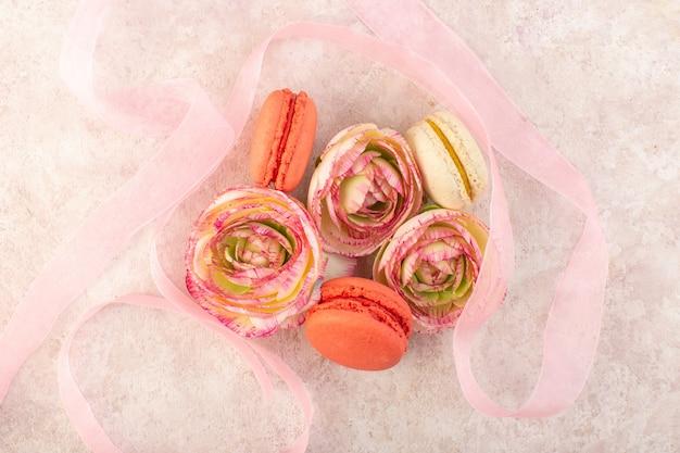 Een bovenaanzicht kleurrijke franse macarons lekker met bloemen op het roze koekje van de bureausuiker