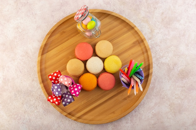 Een bovenaanzicht kleurrijke franse macarons met snoepjes op het roze snoepje van het de cakekoekje van de bureausuiker