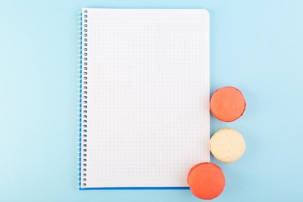 Een bovenaanzicht kleurrijke franse macarons met voorbeeldenboek op het blauwe snoepje van de het koekjessuiker van de bureaucake