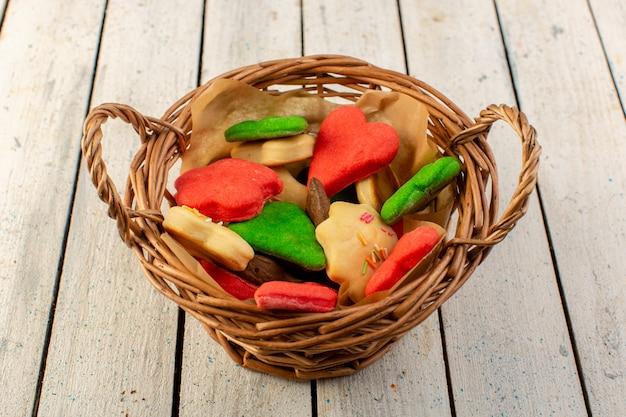 Een bovenaanzicht kleurrijke heerlijke koekjes verschillend gevormd binnen bruine mand op het grijze oppervlak