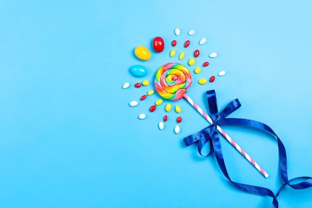 Een bovenaanzicht kleurrijke lolly met roze-witte stok blauwe boog en veelkleurige snoepjes op de blauwe achtergrond verjaardagsfeestje