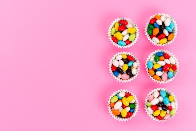 Een bovenaanzicht kleurrijke snoepjes in papieren verpakkingen op roze