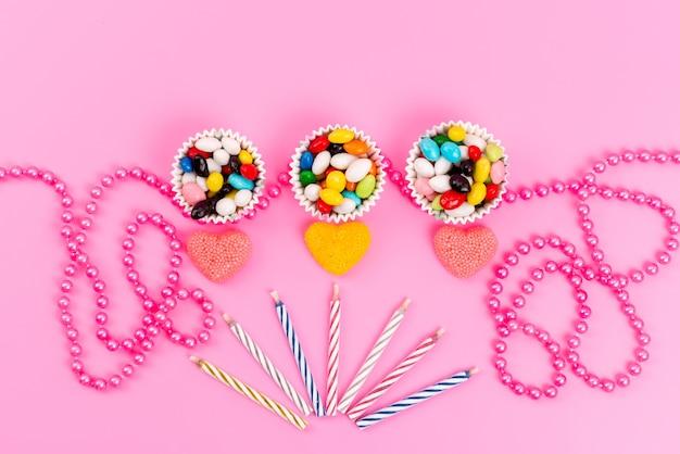 Een bovenaanzicht kleurrijke snoepjes in papieren verpakkingen samen met kaarsen en sieraden op roze