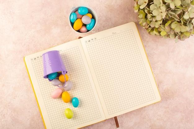 Een bovenaanzicht kleurrijke snoepjes lekker met voorbeeldenboek op het roze bureau snoep bonbon kleur zoet
