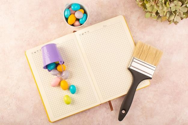 Een bovenaanzicht kleurrijke snoepjes met penseel en voorbeeldenboek op de roze zoete suikerkleur van het bureausuikergoed