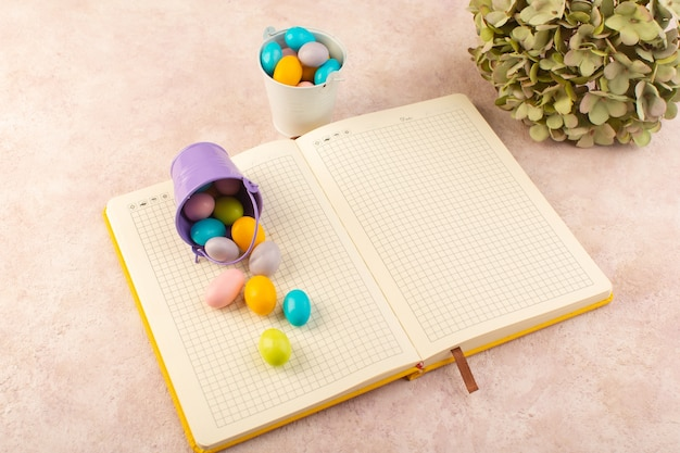 Een bovenaanzicht kleurrijke snoepjes met voorbeeldenboek op het roze bureau kleur zoete suiker goodie