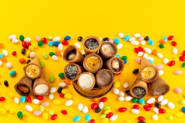 Een bovenaanzicht kleurrijke snoepjes samen met hoornijs op geel