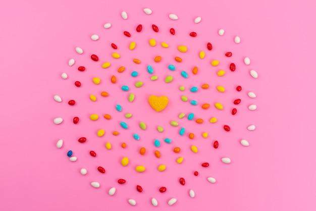Een bovenaanzicht kleurrijke snoepjes vormen een cirkel op roze