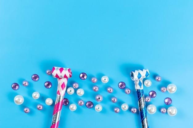 Een bovenaanzicht kleurrijke verjaardag fluitjes samen met kleine sieraden ballen geïsoleerd op blauw