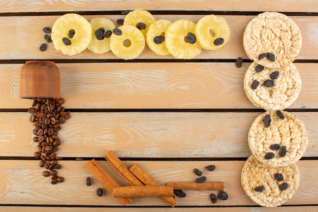 Een bovenaanzicht koffie zaden met gedroogde ananas kaneel en crackers op de crème rustieke tafel koffiezaad drank foto graan