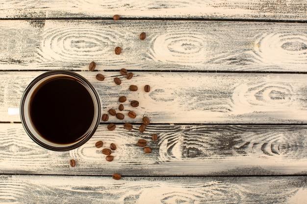 Een bovenaanzicht kopje koffie met bruine koffiezaden op het grijze rustieke bureau drinkt koffiekleur