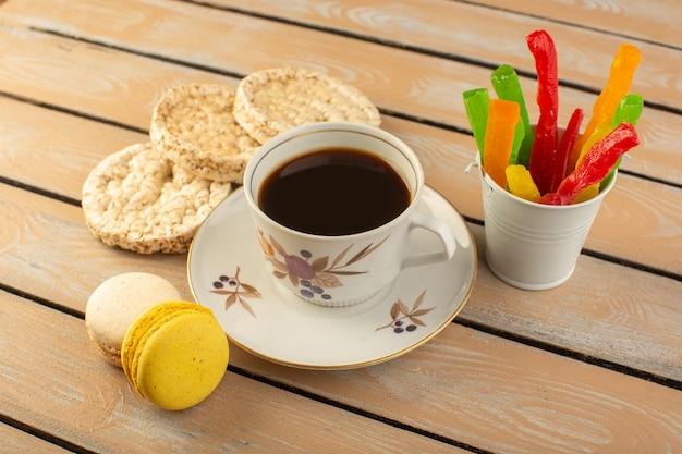 Een bovenaanzicht kopje koffie warm en sterk met franse macarons en marmelade op de crèmekleurige rustieke tafel drink koffie foto koekje