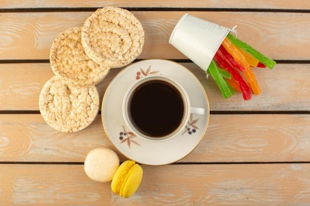 Een bovenaanzicht kopje koffie warm en sterk met franse macarons en marmelade op de crèmekleurige rustieke tafel drink koffie foto sterk