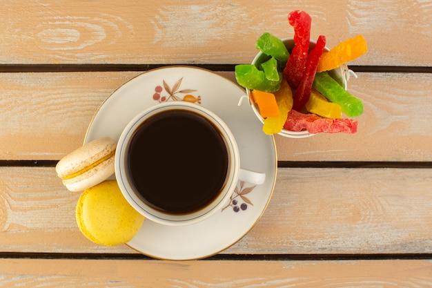 Een bovenaanzicht kopje koffie warm en sterk met franse macarons en marmelade op het crèmekleurige rustieke bureau drink koffie foto sterk