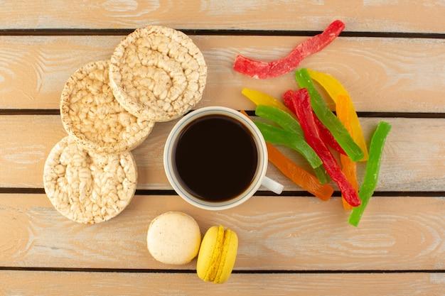 Een bovenaanzicht kopje koffie warm en sterk met franse macarons en marmelade op het crèmekleurige rustieke bureau drink koffie foto zoet