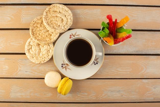 Een bovenaanzicht kopje koffie warm en sterk met franse macarons en marmelade op het crèmekleurige rustieke bureau drinken koffie foto sterk koekje