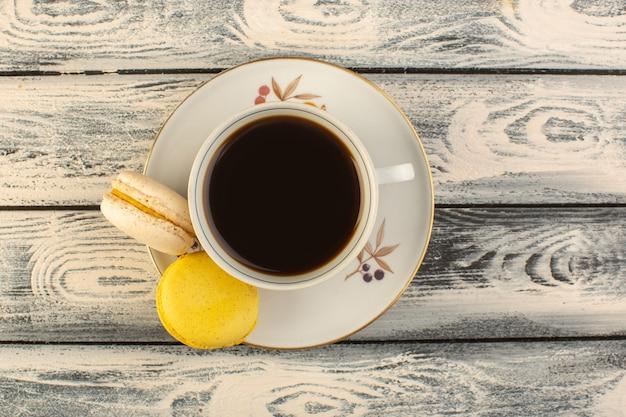 Een bovenaanzicht kopje koffie warm en sterk met franse macarons op de grijze rustieke koffie warme drank