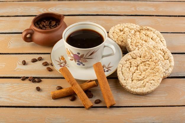 Een bovenaanzicht kopje koffie warm en sterk met verse bruine koffiezaden kaneel en crackers op de crème rustiek bureau koffie zaad drankje foto graan
