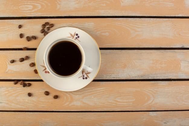 Een bovenaanzicht kopje koffie warm en sterk met verse bruine koffiezaden op de crème rustieke bureau koffie zaad drankje foto graan
