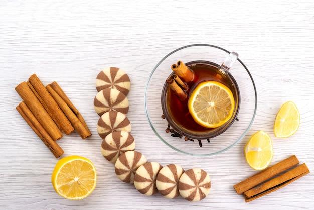 Een bovenaanzicht kopje thee met citroenkoekjes en kaneel op wit, theedessert snoep