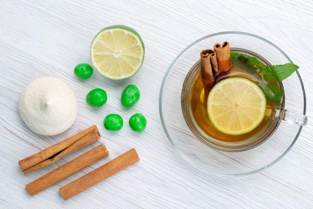 Een bovenaanzicht kopje thee met citroenmunt en kaneel op wit, theedessert snoep