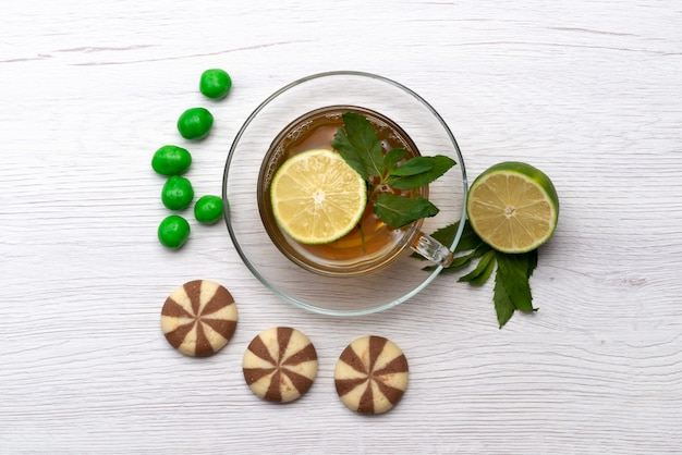 Een bovenaanzicht kopje thee met citroensuikergoed en koekjes op wit, theedessert snoep