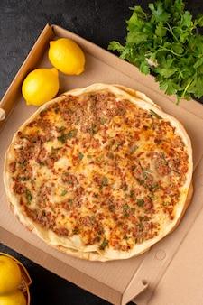 Een bovenaanzicht lahmacun deeg met gehakt met greenies en citroen in kartonnen doos smakelijke gebak maaltijd