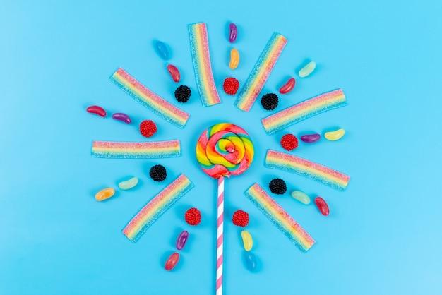 Een bovenaanzicht marmelade en lollies kleurrijk heerlijk op blauwe, regenboogkleuren suiker