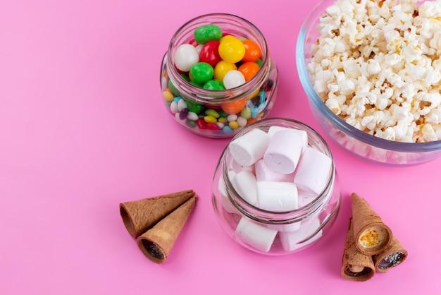 Een bovenaanzicht marshmallows en popcorn samen met gekleurde snoepjes op roze, suikerkleur confituur