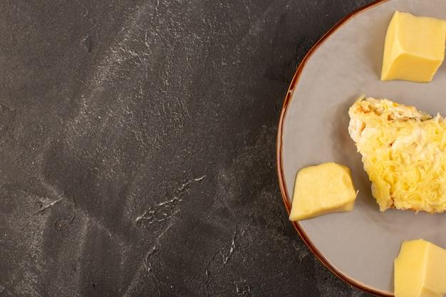 Een bovenaanzicht mayyonaised groentesalade met binnen kip en verse kaas binnen plaat op de grijze snack van de de maaltijdschotel van het bureausalade