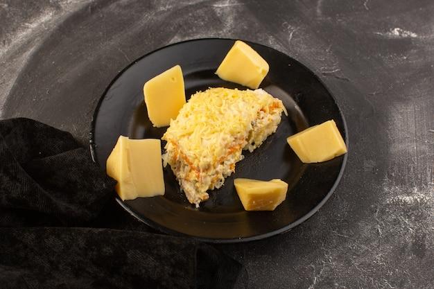 Een bovenaanzicht mayyonaised groentesalade met verse kaas in zwarte plaat op de grijze maaltijd van het bureausalade