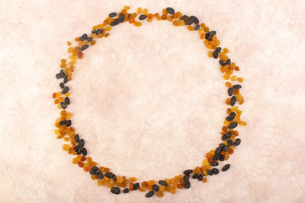 Een bovenaanzicht oranje gedroogde rozijnen met zwarte gedroogde vruchten die cirkel op roze vormen