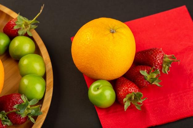 Een bovenaanzicht oranje kersen-pruim aardbeien op het rode weefsel geïsoleerd mellow rijp sappige pulpy vitamine