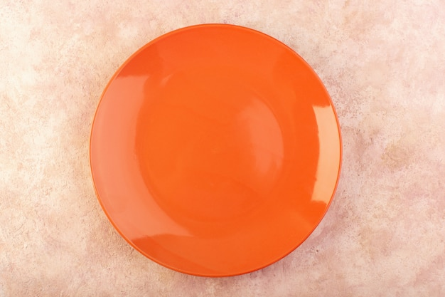 Een bovenaanzicht oranje ronde plaat leeg glas gemaakt geïsoleerde maaltijd tafel