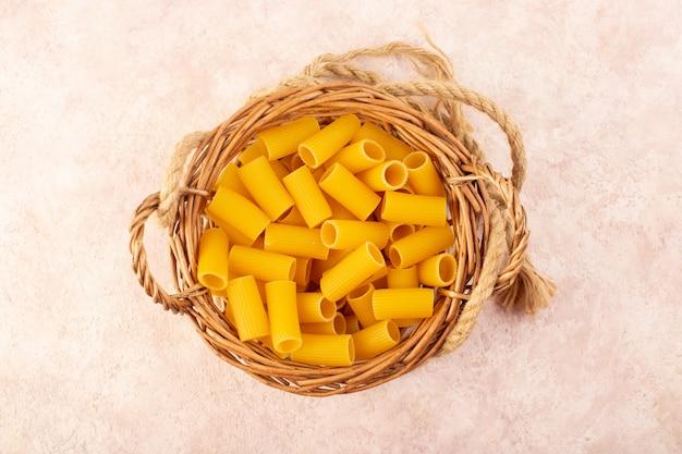 Een bovenaanzicht rauwe italiaanse pasta geel in een mandje samen met touwen op roze