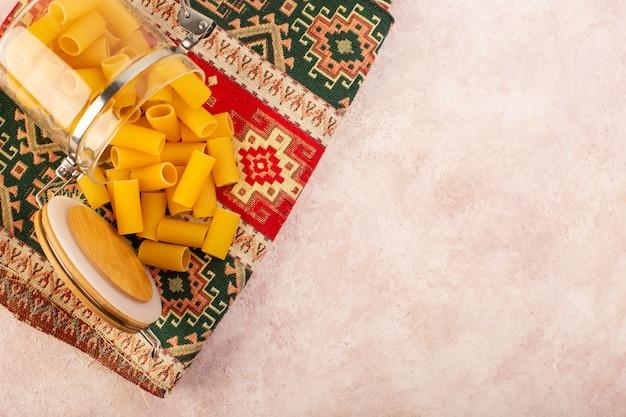 Een bovenaanzicht rauwe italiaanse pasta in kleine glazen ketel op kleurrijk tapijt