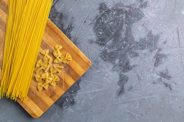 Een bovenaanzicht rauwe italiaanse pasta klein en lang gevormd op de grijze italiaanse maaltijd van het bureau pasta