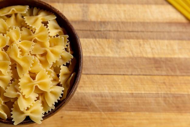 Een bovenaanzicht rauwe italiaanse pasta weinig gevormd binnen bruine plaat op de houten bureau pasta italiaans eten maaltijd