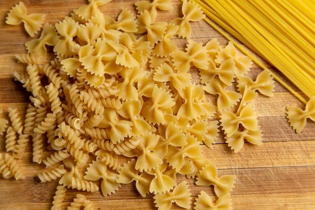 Een bovenaanzicht rauwe italiaanse pasta weinig gevormd op de houten bureau pasta italiaans eten maaltijd