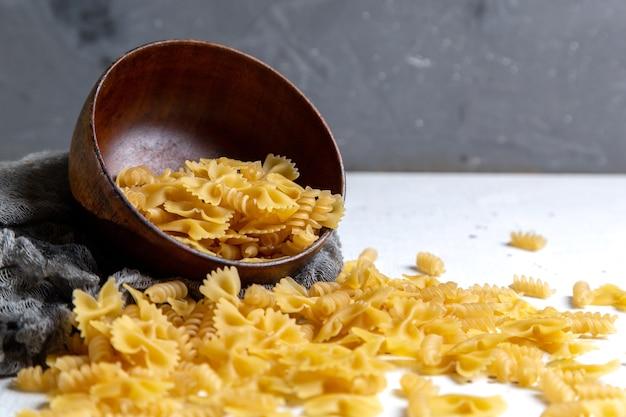 Een bovenaanzicht rauwe italiaanse pasta weinig gevormd op de licht bureau pasta italiaans eten maaltijd