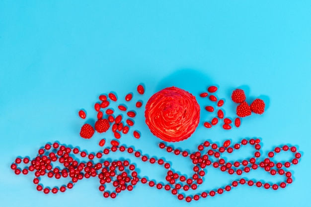 Een bovenaanzicht rode cake met rode snoepjes verspreid over blauw bureau, koekje kleur snoep
